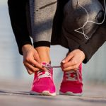 Woman tying pink running shoe