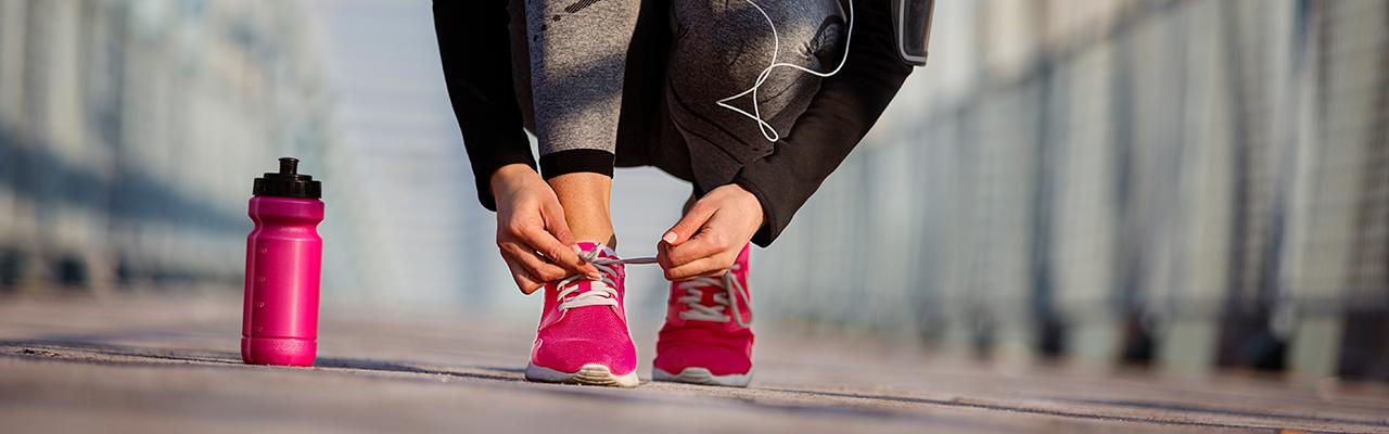 Woman tying pink running shoe