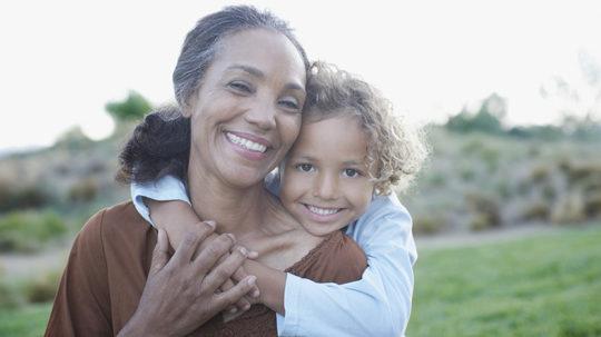 Boy hugging grandmother outdoors