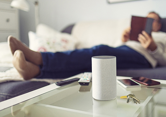 man lies on the couch and talks to virtual assistants