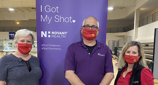 Three employees in masks volunteering at a Novant Health vaccination clinic