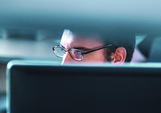 Man Working Behind Computer Monitors