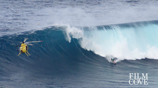 surfer on a large ocean swell with yellow helicopter hovering nearby
