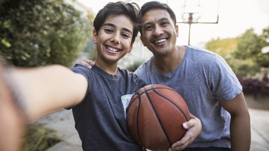 father and son taking a selfie outdoors whilst playing basketball