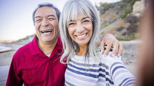 senior couple taking a selfie at the beach