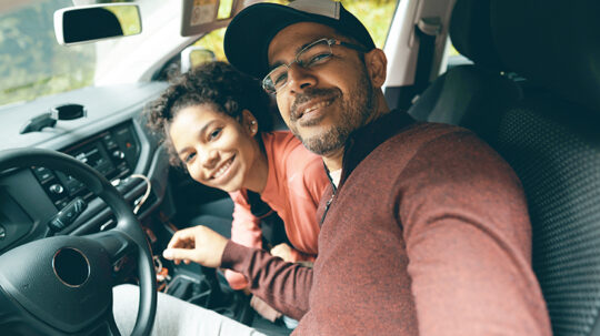 Father in driver seat leaning towards daughter in passenger seat, taking a selfie
