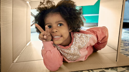 close-up of toddler holding fingers in a peace sign lying inside open cardboard box