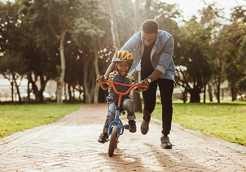 Ecstatic little boy learning to ride a bicycle with his father