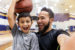 father takes selfie while son holds a basketball on head
