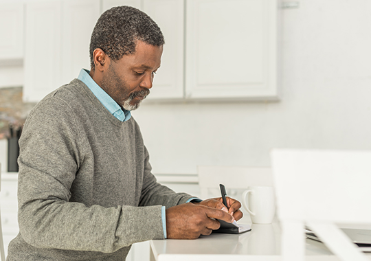 man wearing a sweater sitting at table and writing in notebook