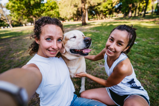 two young women with dog in park