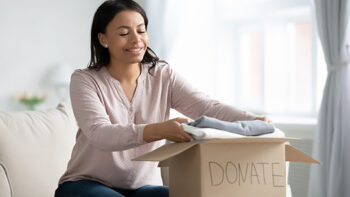 woman sitting on couch packing clothes in donation box