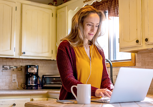 Woman in bright kitchen working on laptop.