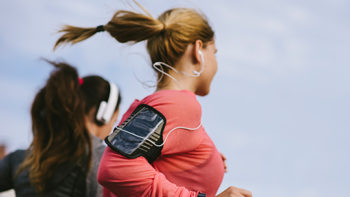 Two friends jogging with headphones and fitness trackers