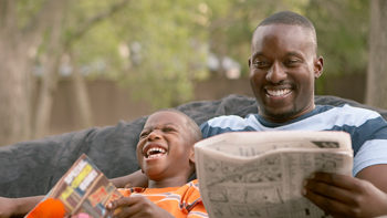 Father and son reading and laughing together outdoors