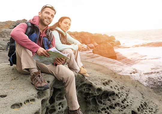 Young couple hiking, sitting on top of the rocks and enjoying the view
