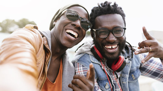 Two ecstatic friends taking a selfie and laughing