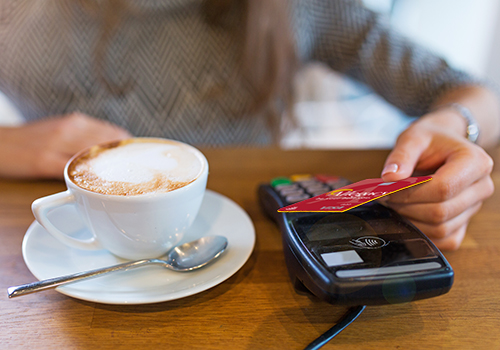 Woman using tap to pay with Allegacy debit card in coffee shop