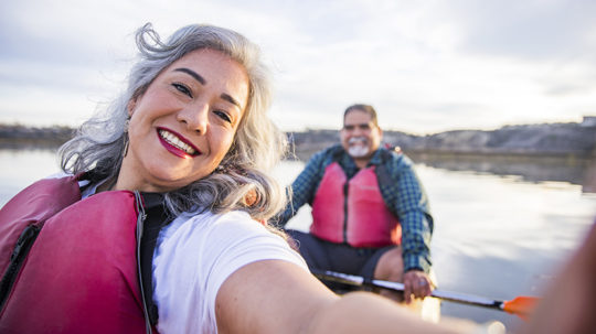 Senior couple kayaking woman taking a selfie with man in the background