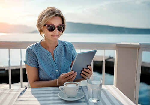 Mature woman managing finances on a tablet, while on vacation