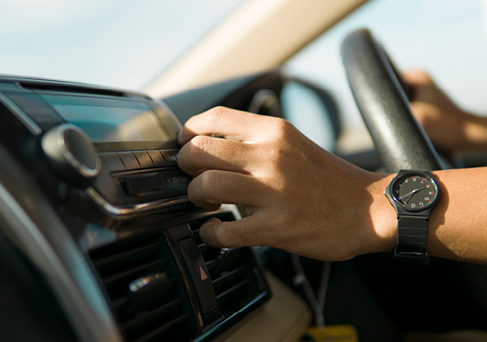 close up of mans hand reaching to adjust stereo volume in car