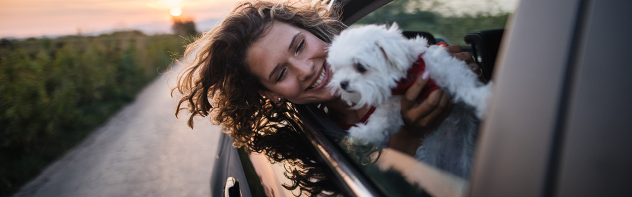 young woman holding white puppy at car window hair of both blowing in the breeze