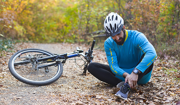 Young man sitting on ground, fallen from a sprained ankle injury during cycling. About 25 years old, Caucasian male.