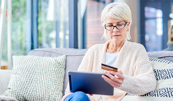Shot of a senior woman using a digital tablet and credit card on the sofa at home