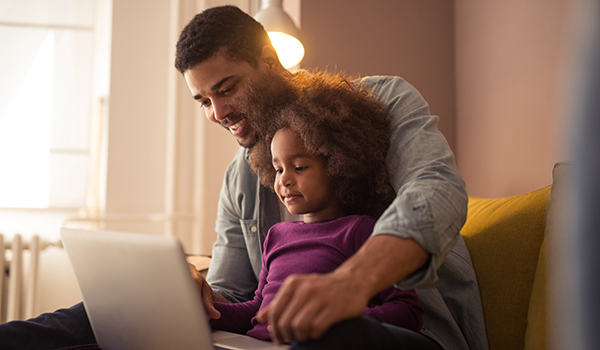 African american dad and his daughter using a computer.