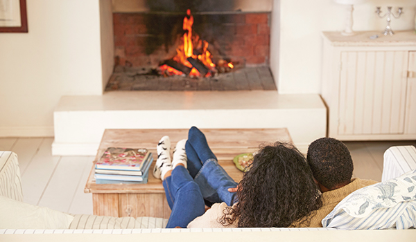 Couple looking at fire in fireplace