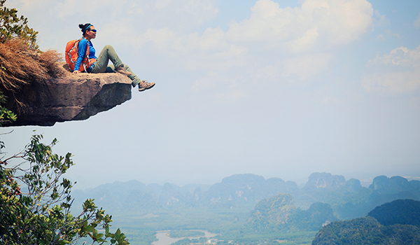 Young woman sitting on edge of mountain