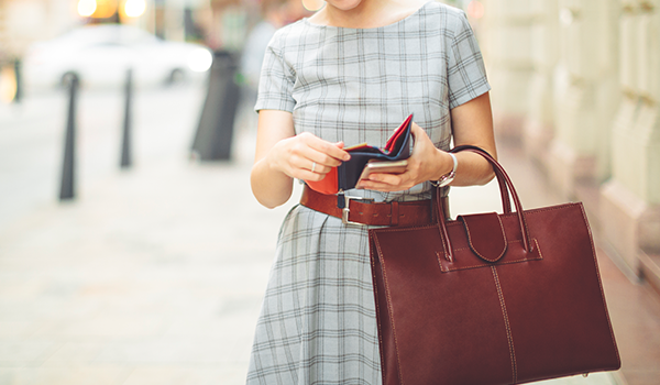 woman in dress on sidewalk looking in a red wallet