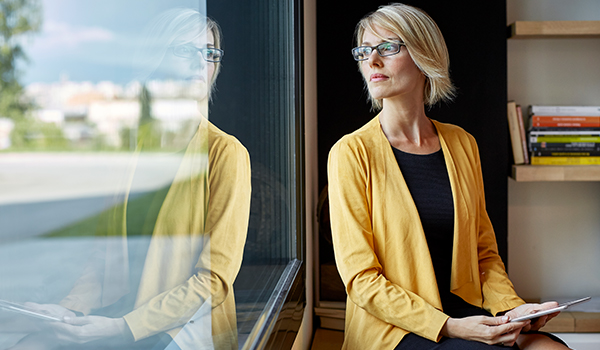 Woman in yellow jacket gazing out window