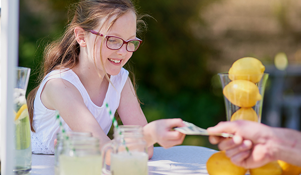 Girl taking money at lemonade stand