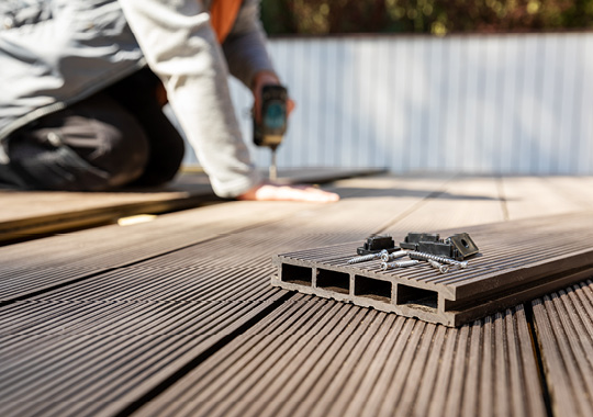man using drill in background with all-weather decking and screws in foreground