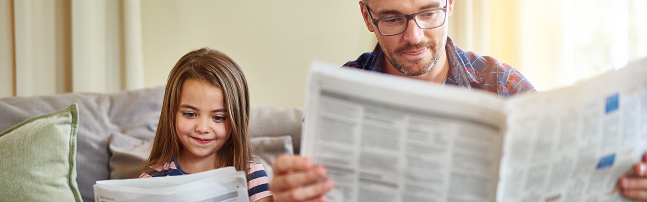 dad and young daughter reading newspaper together on couch at home
