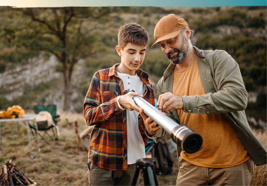 father and son positioning long range telescope outdoors