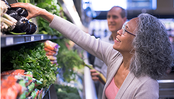 woman reachin gfor produce in grocery store