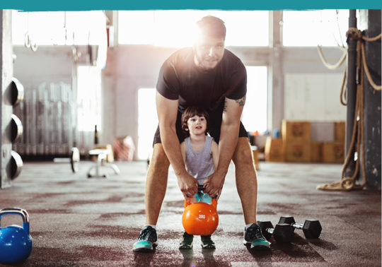 dad helping son lift weight in open gym