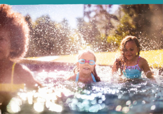 three young girls wearing gogles and splashing in a backyard pool in the sunshine