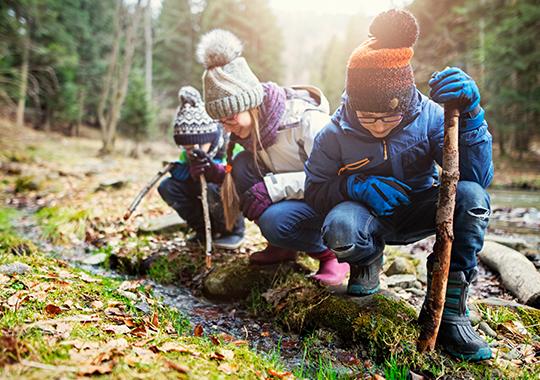 kids in winter coats and toboggans exploring the woods