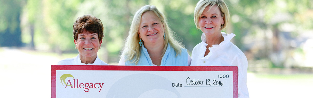 women holding up giant check